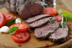 Roast beef. Sliced roast beef and vegetables on a cutting board Royalty Free Stock Image