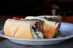 Roast beef sub. Sandwich cut in two on a paper plate on a stone and wood table Stock Images
