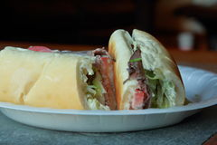 Roast beef sub. Sandwich cut in two on a paper plate on a stone and wood table Royalty Free Stock Photos