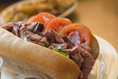 Roast Beef Sub Sandwich. Roast beef on torpedo roll with tomato basil and fresh mozzarella cheese Royalty Free Stock Images