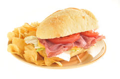 Roast beef submarine sandwich. A roast beef submarine sandwich with potato chips Royalty Free Stock Images