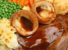 Roast Beef Sunday Dinner. Traditional Sunday roast beef dinner with Yorkshire puddings and gravy Stock Images