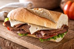 Roast Beef and Swiss on Baguette. A delicious roast beef sandwich with swiss cheese, lettuce and tomato on a french bread baguette stock photography