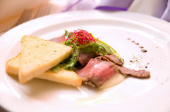 Roast Beef and toast with arugula on white plate Stock Image