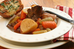 Roast Beef with Vegetables. Roast beef with potatoes, carrots, celery; herbed garlic bread on side Stock Image