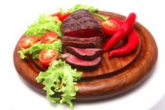 Roast beef on wooden plate Royalty Free Stock Photo