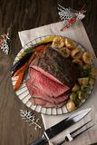Roast Beef With Yorkshire Puddings. Peppercorn roast beef with herbed Yorkshire puddings garnished with roasted vegetables Stock Image