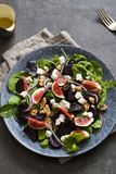 Roast beetroot, figs and feta salad. Autumn salad with roast beetroot, figs and feta cheese on the bed of green mixed salad leaves royalty free stock photo