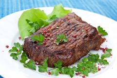 Roast big steak  on green dish close up Royalty Free Stock Photo