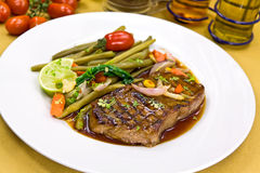 Roast big steak sirloin on green dish close up Stock Images