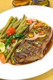 Roast big steak sirloin on green dish close up.  Royalty Free Stock Image