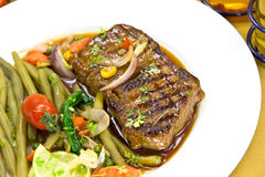 Roast big steak sirloin on green dish close up Stock Photos