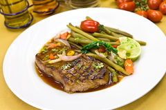 Roast big steak sirloin on green dish close up Royalty Free Stock Images
