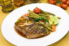 Roast big steak sirloin on green dish close up.  Royalty Free Stock Images