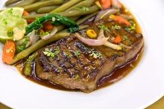 Roast big steak sirloin on green dish close up Stock Photography