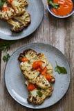 Roast cauliflower steak. Vegetarian meal of roast cauliflower steak with herbs and red pepper sauce Stock Photos