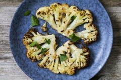 Roast cauliflower steak. Vegetarian meal of roast cauliflower steak with herbs Royalty Free Stock Image