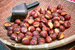 Roast chestnuts on basket. For sale in market Stock Photos