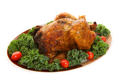 Roast chicken. A spicy whole roast chicken on a platter Royalty Free Stock Photo