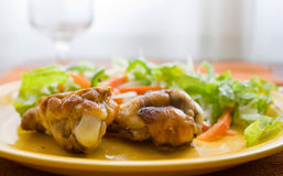 Roast chicken. Lying on a yellow plate with a salad mixed Royalty Free Stock Photo