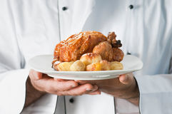 Roast chicken. Chef presenting and serving his roast chicken with potatoes Royalty Free Stock Photos