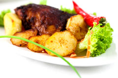 Roast chicken with baked potatoes stock images