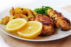 Roast chicken with baked potatoes and green. Seasoned grilled chicken with baked potatoes, green and lemon royalty free stock photography