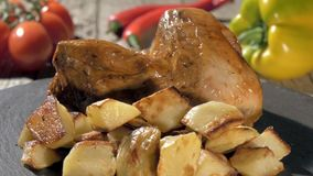 Roast chicken with baked potatoes on stone plate rotating stock video