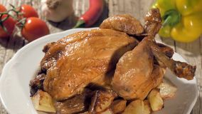 Roast chicken with baked potatoes on white plate rotating stock video footage