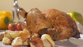 Roast chicken with baked potatoes on white plate rotating stock footage