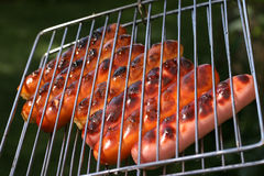 Roast chicken and beef sausages on grill stock images