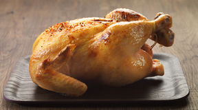 Roast chicken. On brown wooden plate Stock Photography