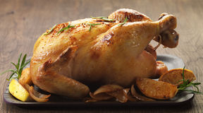 Roast chicken. And caramelized onions on wooden plate Stock Images