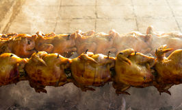 Roast chicken charcoal fire. Rotating spit roast chicken on an open charcoal fire on the roadside Thailand Stock Photography