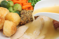 Roast Chicken Dinner. With gravy being poured. Sharp focus on stuffing and adjacent potato Royalty Free Stock Photography