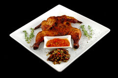 Roast chicken on a disy. Roast chicken on a dish on a black background royalty free stock photo