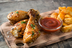 Roast chicken drumsticks and chips on wooden background Royalty Free Stock Photo