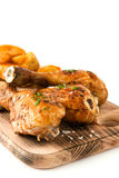 Roast chicken drumsticks on cutting board isolated on white background Royalty Free Stock Photo