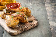 Roast chicken drumsticks on cutting board  and rustic wood Royalty Free Stock Photos