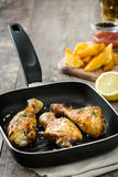 Roast chicken drumsticks on a fried pan Stock Image
