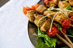 Roast Chicken filet kebab on bamboo sticks. With salad and cherry tomatos Stock Photos