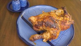 Roast chicken with garlic on a blue plate stock footage