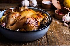 Roast chicken with garlic and lemon in cooking pan Stock Images