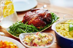 Roast chicken with garnish of green beans on table. Food, culinary and eating concept - roast chicken with garnish of green beans on served table Royalty Free Stock Images