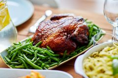 Roast chicken with garnish of green peas on table Stock Images