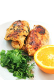 Roast chicken with green and orange. Half orange with green (chopped parsley and dill) and roast chicken stock images