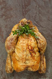 Roast Chicken with Herbs. Roast chicken with fresh herbs.  Overhead view, on rustic stone background Stock Photo