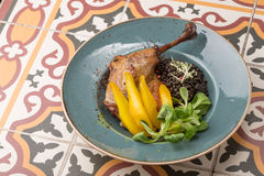 Roast chicken leg with pear and black peas Royalty Free Stock Photography
