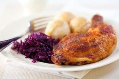 Roast chicken leg with potato dumplings stock photo
