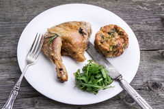 Roast chicken leg with rosemary and herb stuffing. Roast chicken leg with rosemary and herb stuffing served with arugula salad and fresh herbs stock photography